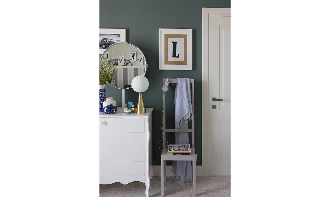 la parete azzurra fa risaltare la cassettiera bianca