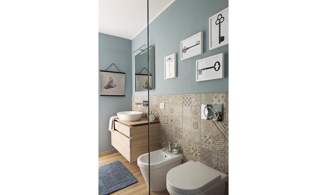 La parete rivestita di cementine dà carattere al bagno