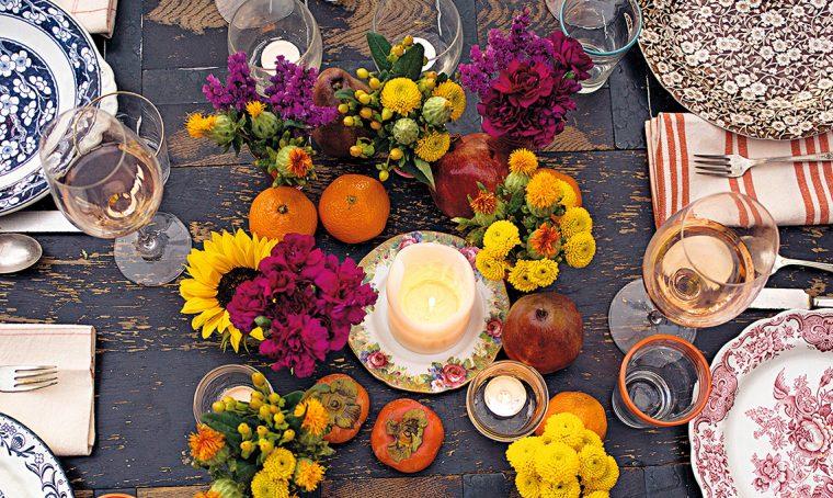 Il centrotavola autunnale con fiori, frutta e candele