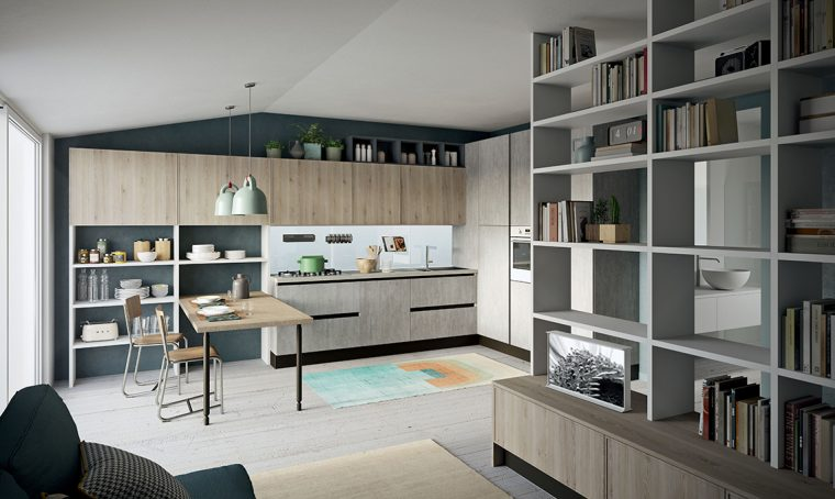 Nel monolocale la cucina a vista con scaffali e penisola