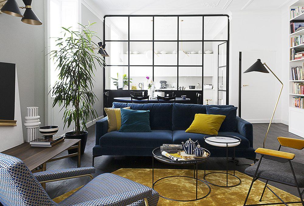 Un appartamento d'epoca con parete vetrata che divide soggiorno e cucina